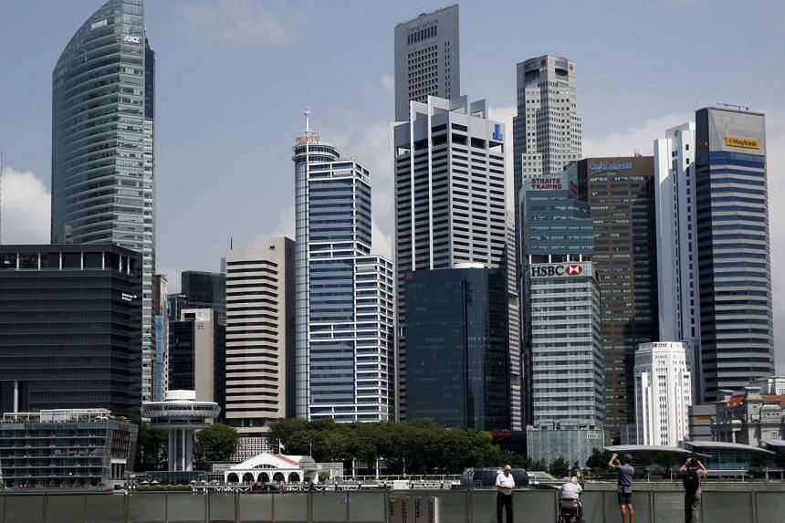 People take photos of the skyline of the central business district in Singapore, on April 27, 2016.