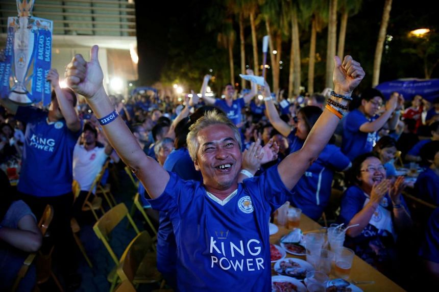 Leicester City fans celebrate after their team scores against Manchester United while watching the game on a big screen, in Bangkok, on May 1, 2016.