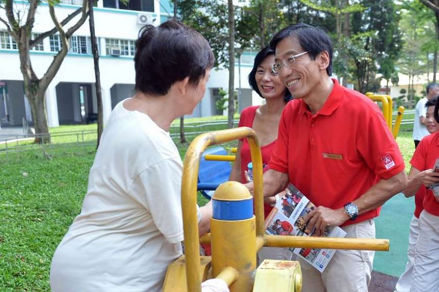 Dr Chee greeting a Bukit Batok resident yesterday. On his right is his wife Huang Chih Mei.