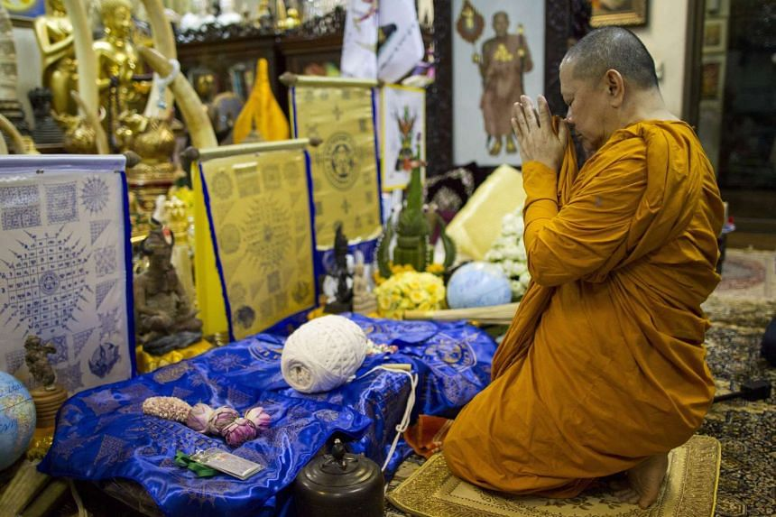 Thai Buddhist monk Phra Prommangkalachan chants next to sacred holy unbeatable Leicester City fabric cloth and talisman at Wat Traimit temple, also known as Golden Buddha temple, in Bangkok, on May 2, 2016.