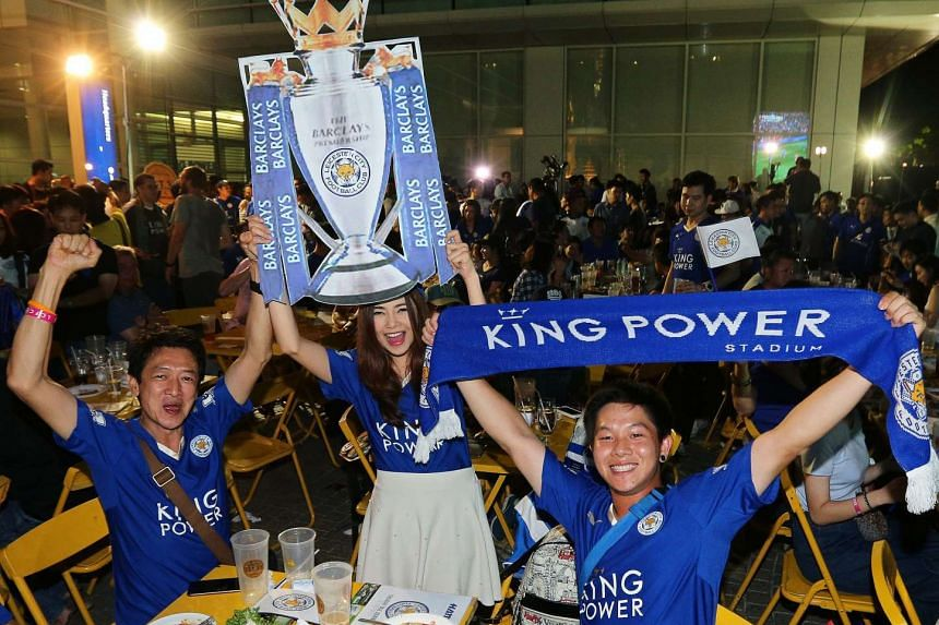 Thai supporters of Leicester City celebrate while watching the English Premier League football match between Manchester United and Leicester on a huge screen outside the King Power Downtown Complex in Bangkok, on May 1, 2016.