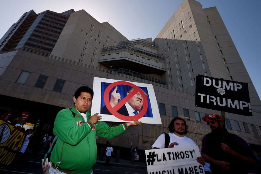 Immigration rights protesters hold posters of Republican presidential hopeful Donald Trump during a May Day rally in Los Angeles, on May 1, 2016.