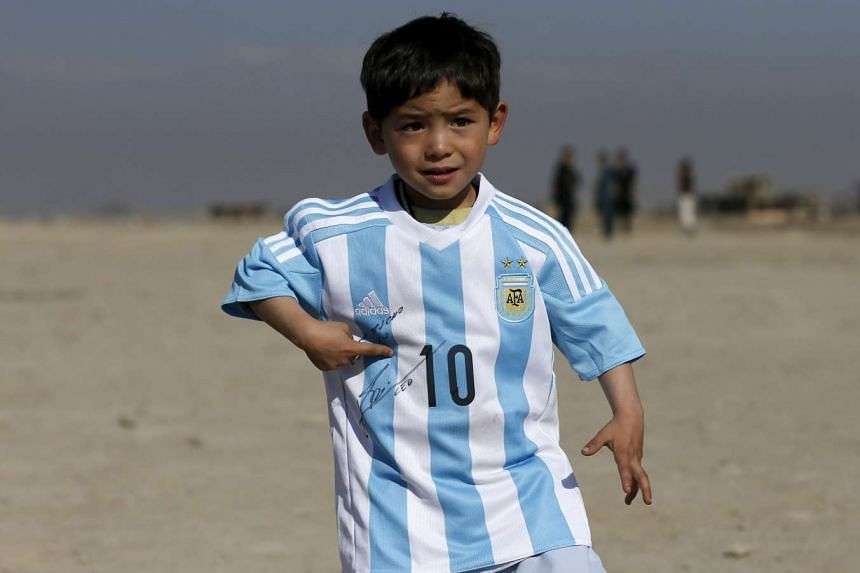 Murtaza Ahmadi wears a shirt signed by Barcelona star Lionel Messi, as he plays football in Kabul, Afghanistan, on Feb 26, 2016.
