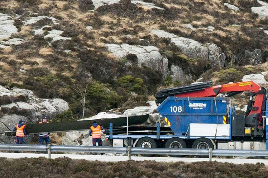 Helicopter rotorblades are loaded onto a truck trailer and brought away from the crash site in Turoy, outside Bergen, Norway, on May 1, 2016.