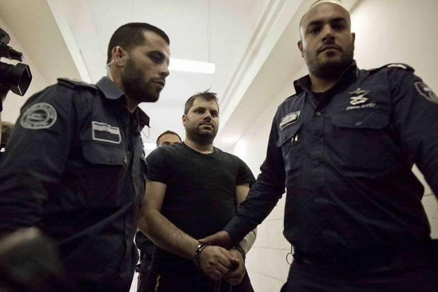 Yosef Haim Ben-David (centre) being escorted to the Israeli District Court in Jerusalem on May 3, 2016.