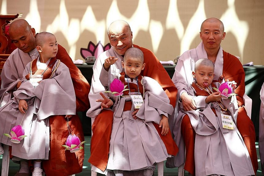 """Boy monks sitting with older Buddhist monks during the """"Children becoming Buddhist monks"""" ceremony at the Jogyesa temple, the chief temple of the Jogye Order of Korean Buddhism, in Seoul, South Korea, yesterday. The children will stay at the temple f"""