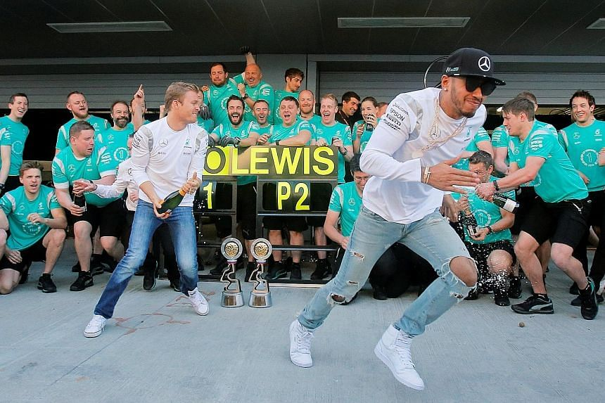 Mercedes drivers Nico Rosberg (left) and Lewis Hamilton celebrate a 1-2 finish at the Russian Grand Prix with their team.