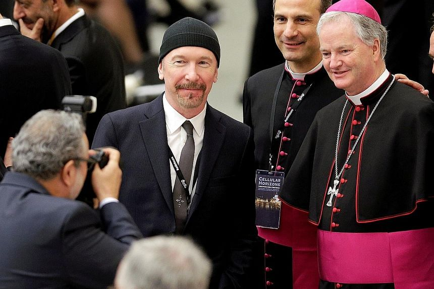 U2 guitarist The Edge poses with Irish bishop Paul Tighe (far right) before listening to US Vice-President Joe Biden's address at the Vatican.