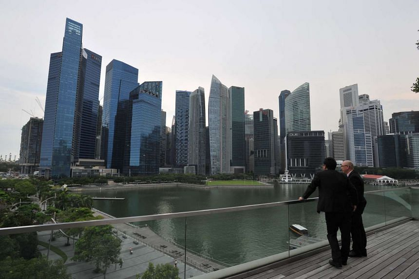 Businessmen view the Singapore skyline at the Marina Bay area.