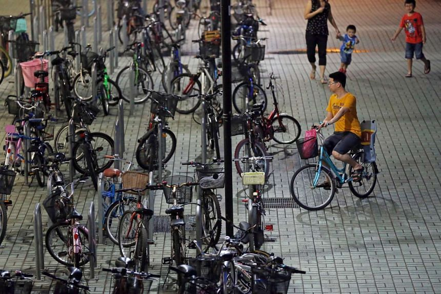 A cyclist arriving at the bicycle parking area near Sengkang MRT Station.