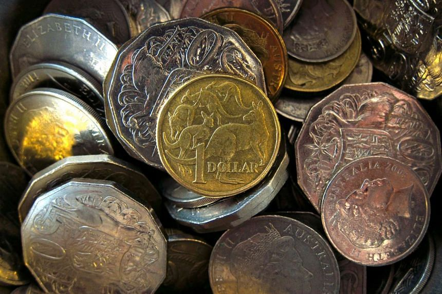 An Australian one dollar coin can be seen amongst various other Australian coins at a store in Sydney, Australia.