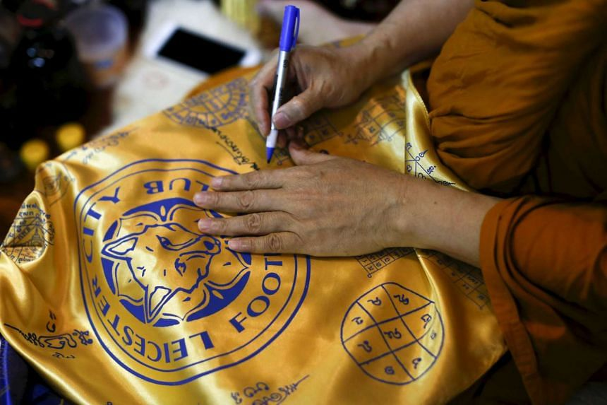 Buddhist monk Phra Prommangkalachan signs holy cloths with Leicester City's logo at the temple in Bangkok, Thailand, on April 18, 2016.