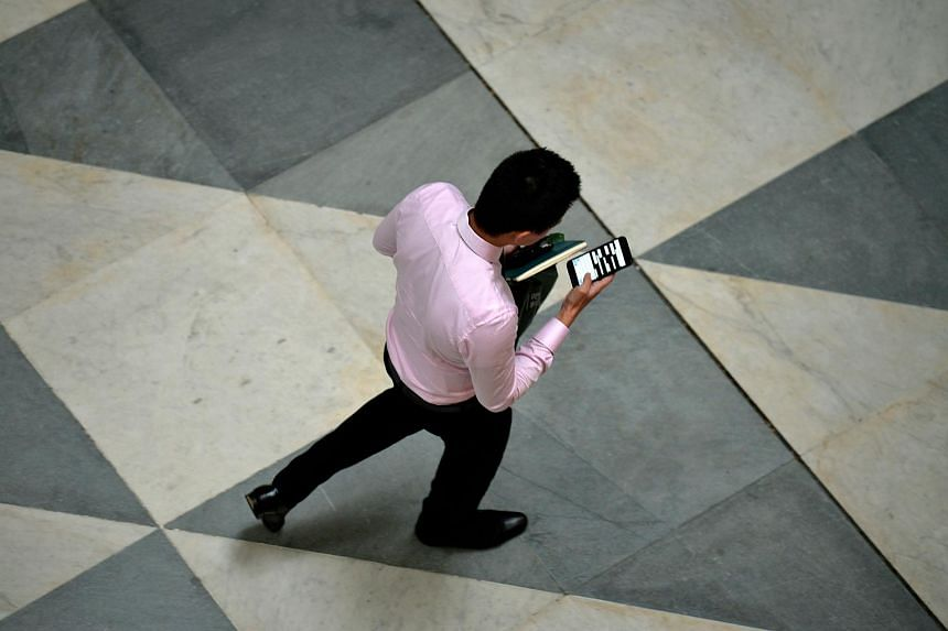 A man checks on his mobile phone along Change Alley during lunch hour in the Central Business District at Raffles Place, on Feb 24, 2016.