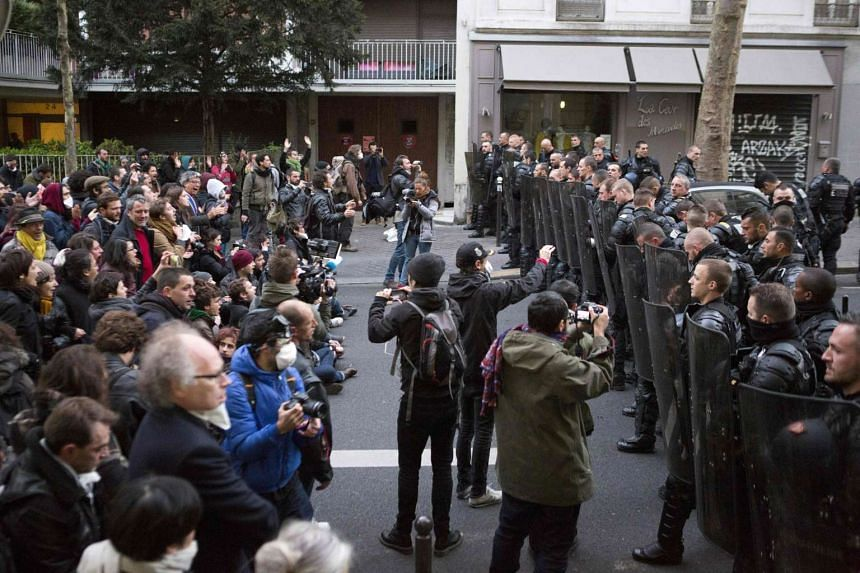 Migrants' supporters face anti-riot policemen to protest against the Jean-Jaurès highschool evacuation in Paris on May 4, 2016.