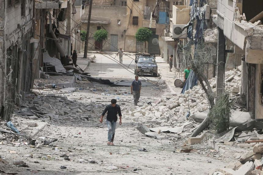 People walk on the rubble of damaged buildings after an airstrike in the rebel held area of Aleppo's Baedeen district, Syria on May 3, 2016.