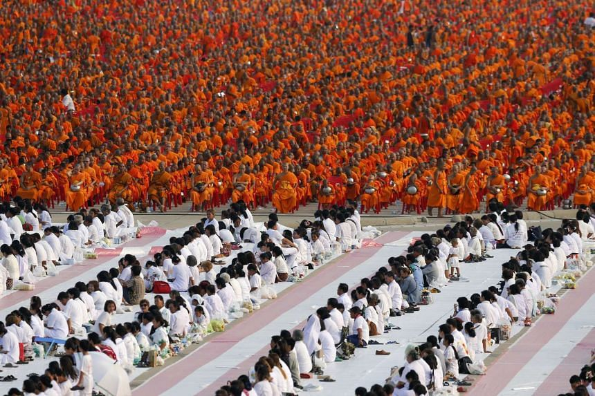 Over 100,000 Buddhist monks and novices gather to receive alms at Wat Phra Dhammakaya temple on April 22, 2016.
