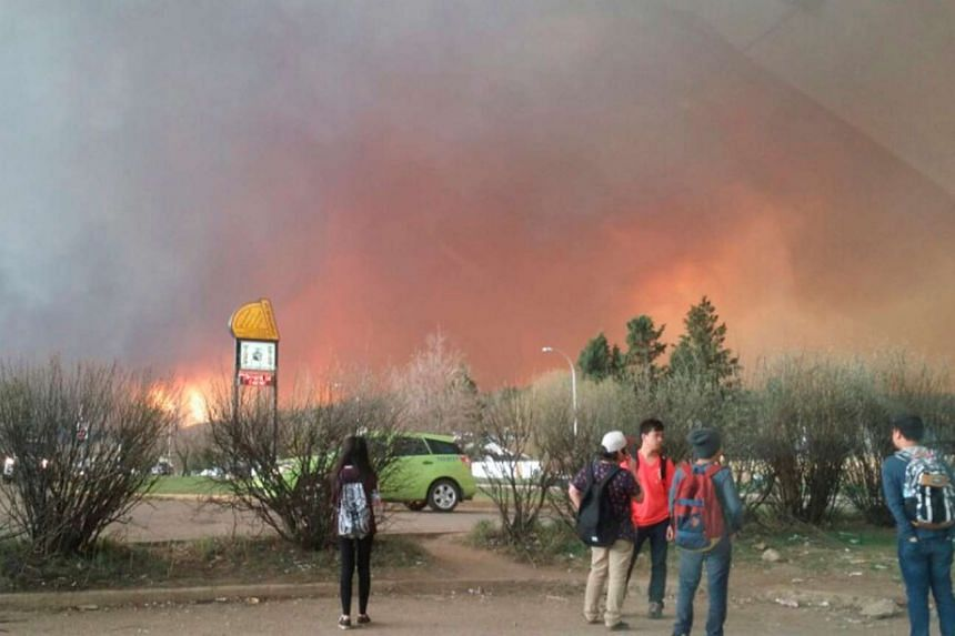 Students from a local high school are released early as a wildfire burns nearby in Fort McMurray on May 3, 2016.