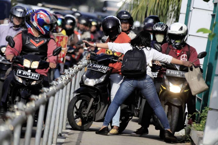 Alfini Lestari (front) blocking a horde of motorbikes from riding down the pavement in Jakarta's busy street.