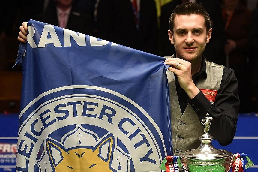 England's Mark Selby holding a Leicester City banner next to his trophy after beating China's Ding Junhui in the final of the World Snooker Championship at the Crucible Theatre in Sheffield.