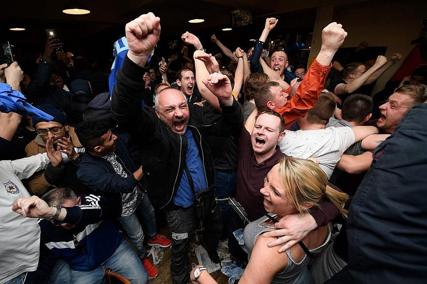 Leicester City fans celebrating their team becoming the English Premier League champions in central Leicester on Monday after Chelsea held Tottenham Hotspur to a 2-2 draw.