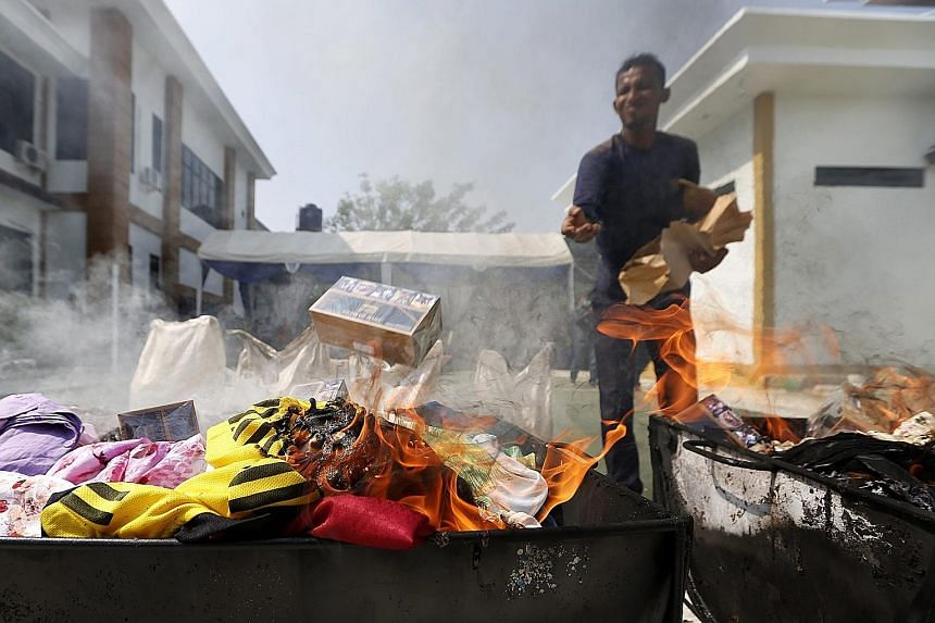 A Customs officer burning illegal products at the Banda Aceh Customs headquarters in Indonesia yesterday. Indonesia has a big market for illegal goods coming from China and other Asian countries.