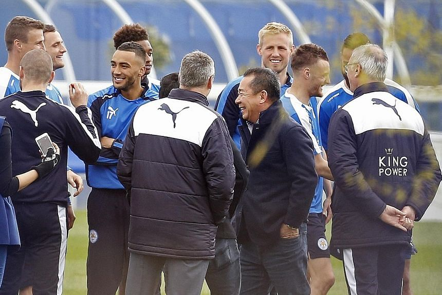Leicester City's Thai chairman Vichai Srivaddhanaprabha (in dark jacket) celebrating the club's title win with coaching staff and players during a training session yesterday. The billionaire has left a distinctly Thai mark on the team.