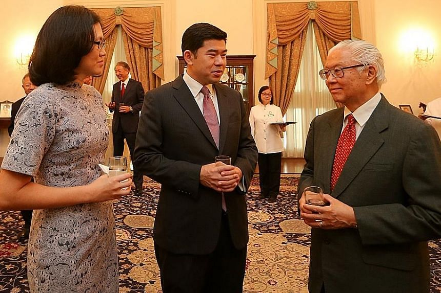 Mr Gabriel Lim, 40, and his wife, Sharon, chatting with President Tony Tan Keng Yam during a reception after Mr Lim was sworn in as Second Permanent Secretary (Ministry of Communications and Information) at the Istana yesterday. Mr Lim, a former prin