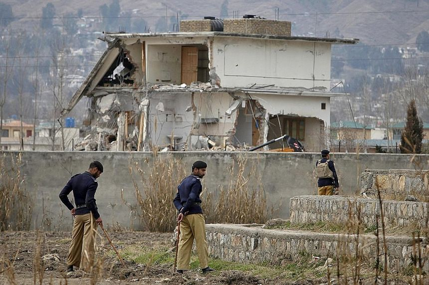 Policemen standing guard during 2012 demolition works at the Abbottabad compound (above) where Osama (left) was killed. The US Central Intelligence Agency marked the fifth anniversary of the May 2, 2011 raid by live-tweeting it (right), as if it was
