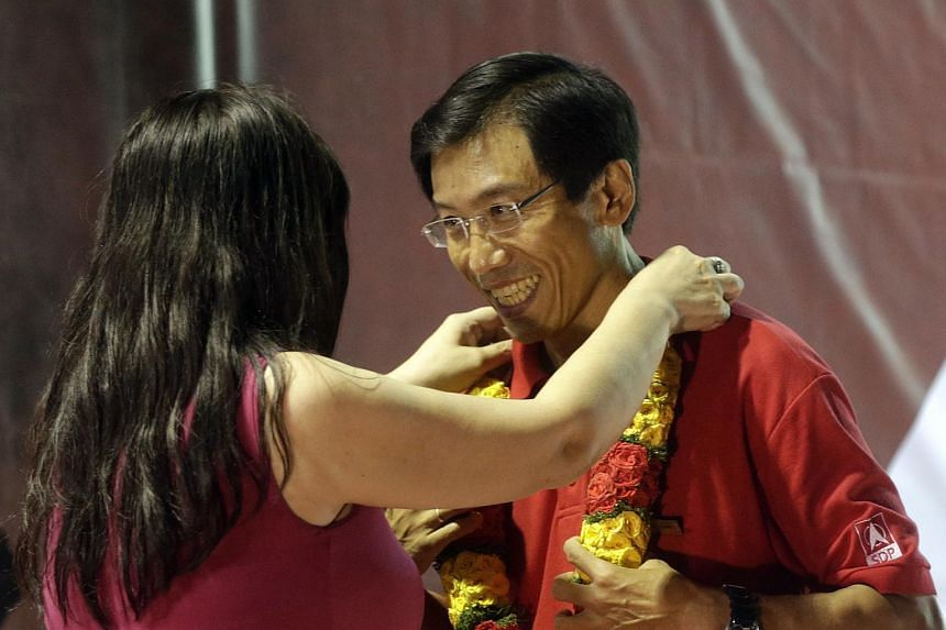 SDP chief Chee Soon Juan being presented with a garland by a female supporter after the Singapore Democratic Party rally at the field along Bukit Batok Industrial Park A on May 3, 2016.