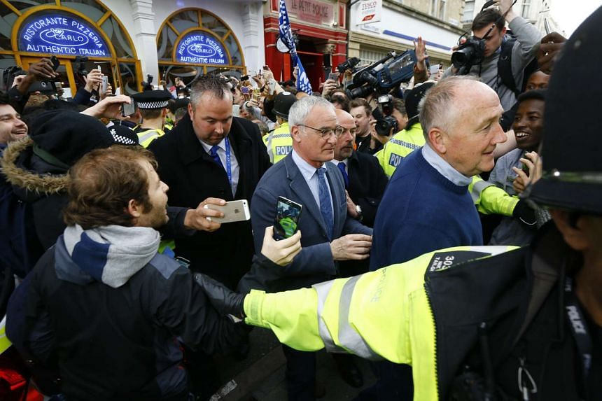Cheering Leicester fans surrounding Leicester City manager Claudio Ranieri as he leaves the San Carlo restaurant in Leicester, Britain, on May 3, 2016.