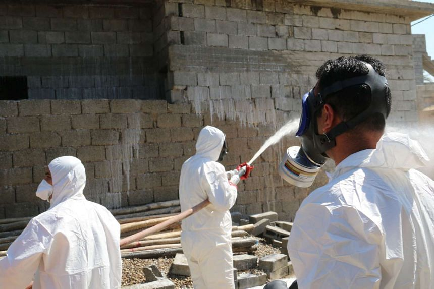 Civil defence personnel spraying and cleaning areas in the town of Taza, Iraq, after a suspected chemical attack by ISIS, on March 13, 2016,