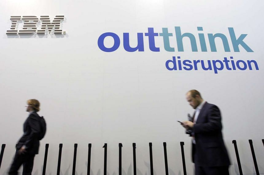 People walk past an IBM logo during the Mobile World Congress in Barcelona, Spain, on Feb 25, 2016.