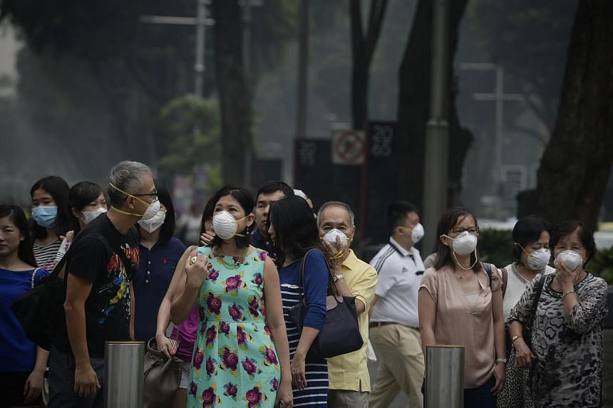 People wearing masks along Orchard Road at around 1pm on Sept 24, 2015. The overall PSI reading at that time was 179-219.