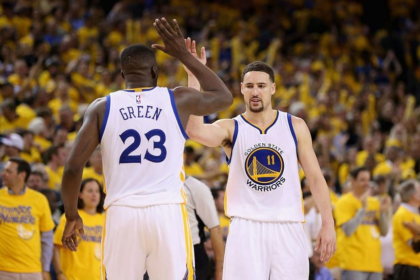 Klay Thompson #11 and Draymond Green #23 of the Golden State Warriors celebrate in the final minute of their victory over the Portland Trail Blazers.