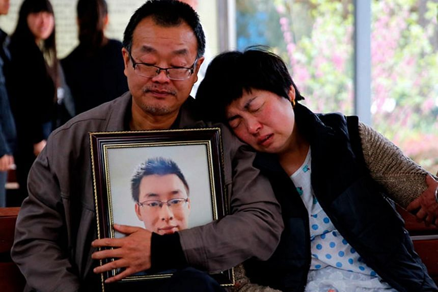 The parents of Wei Zexi, who died of a rare form of cancer, wait outside a funeral home in Xianyang, Shaanxi.
