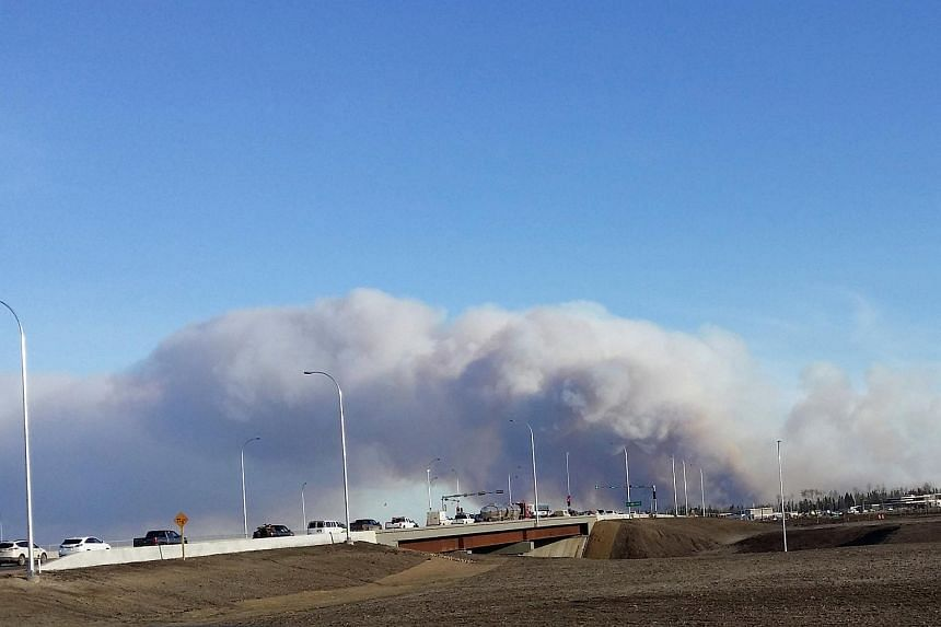 Vehicles are seen on highway 63 as they are detoured near a wildfire burning near Fort McMurray, Alberta.