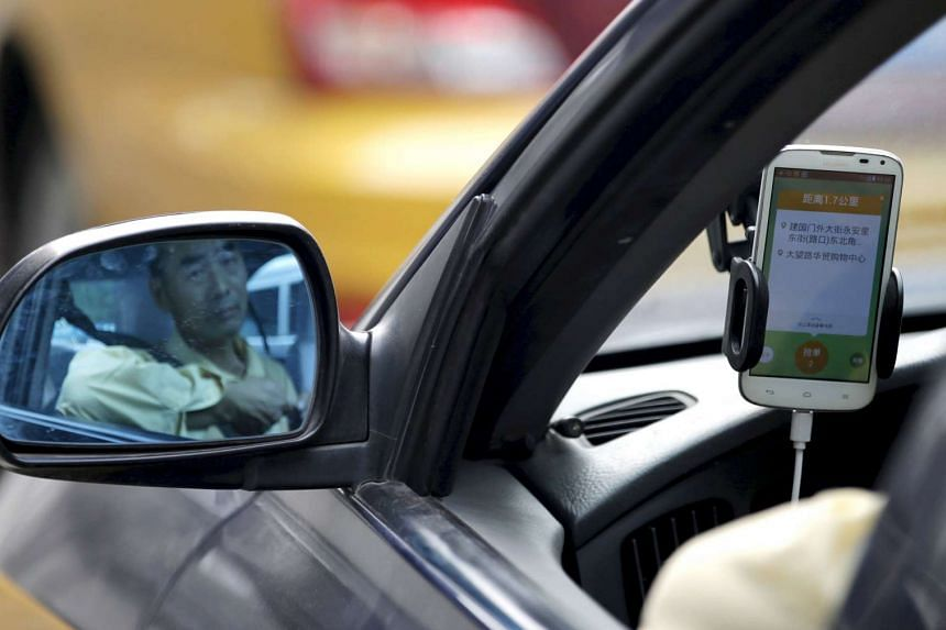 A taxi driver is reflected in a side mirror as he uses the Didi Chuxing car-hailing application in Beijing, China.