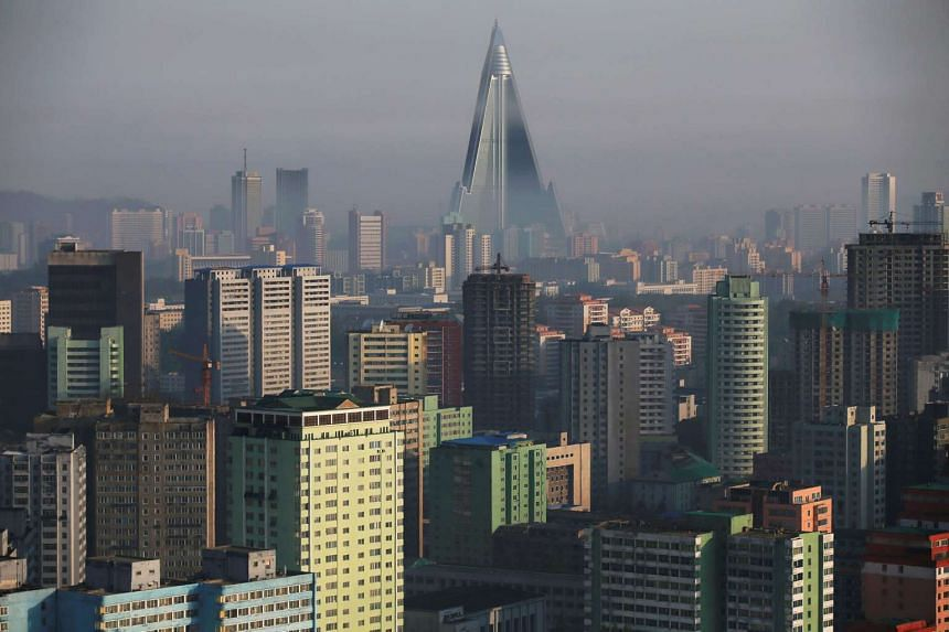 The 105-storey Ryugyong Hotel, the highest building under construction in North Korea, is seen behind a residential building in Pyongyang, on May 5, 2016.