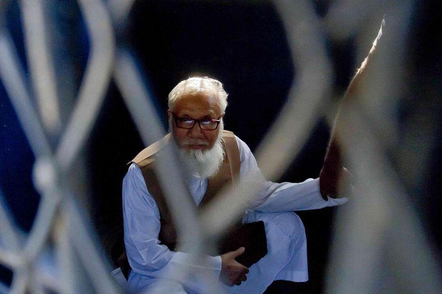 Motiur Rahman Nizami sits inside a van while being taken to a prison after being sentenced at the International Crimes Tribunal court in Dhaka, on Oct 29, 2014.