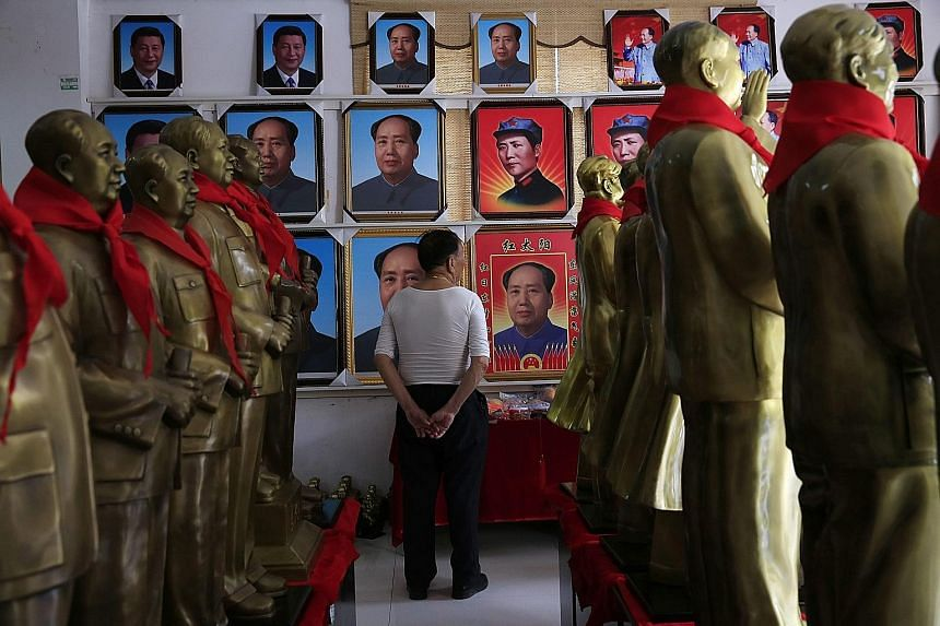 """A visitor gazing at portraits and statues of former Chinese leader Mao Zedong at a souvenir store in Shaoshan in the hilly region of central Hunan province. Shaoshan was Mao's home town, and thousands visit it every day to pay homage to the """"Great He"""