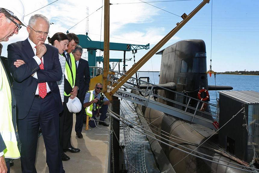Australian Prime Minister Malcolm Turnbull (second from left) looks at a Royal Australian Navy Collins-class submarine at the ASC naval shipyards in Adelaide.