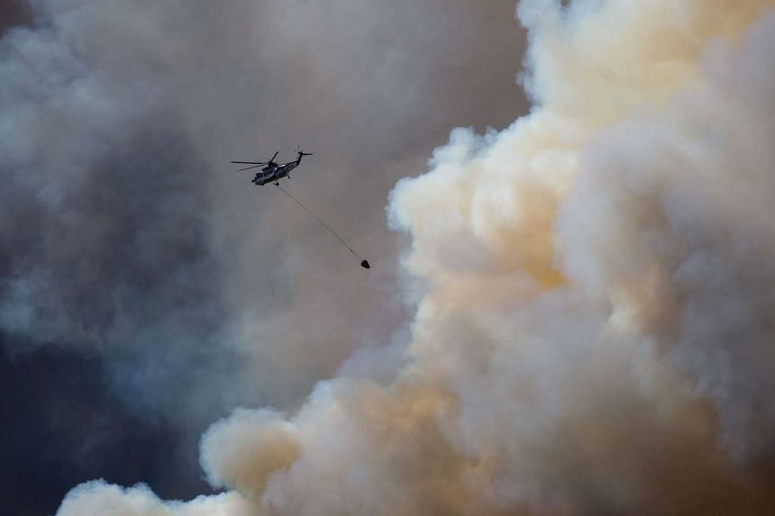A helicopter flies into thick smoke while battling a major forest fire outside of Fort McMurray on May 4, 2016. P