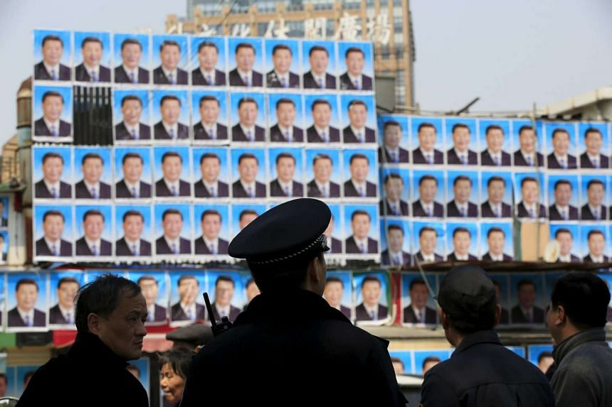 People look at a building covered in hundreds of posters of Chinese President Xi Jinping in Shanghai, China, on March 26, 2016.