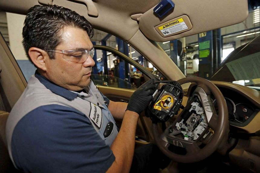 Technician Edward Bonilla holds a recalled Takata airbag inflator in a file photo after he removed it from a Honda Pilot.
