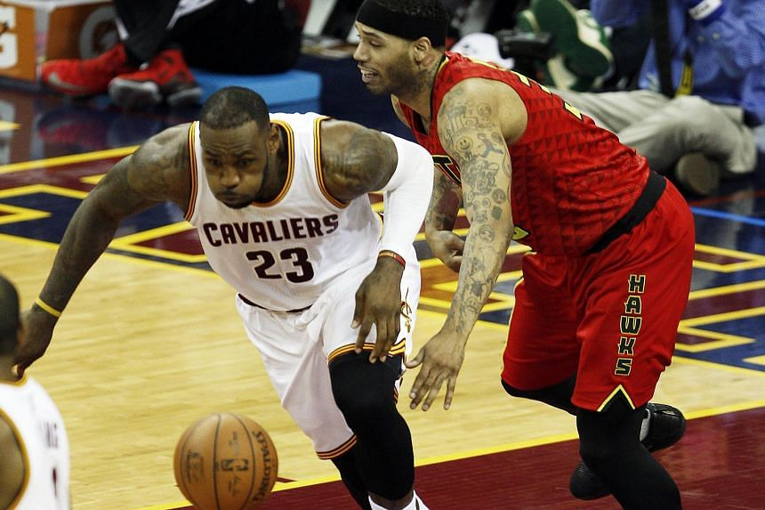 LeBron James (left) of the Cleveland Cavaliers steals a pass intended for Mike Scott of the Atlanta Hawks, on May 2, 2016.