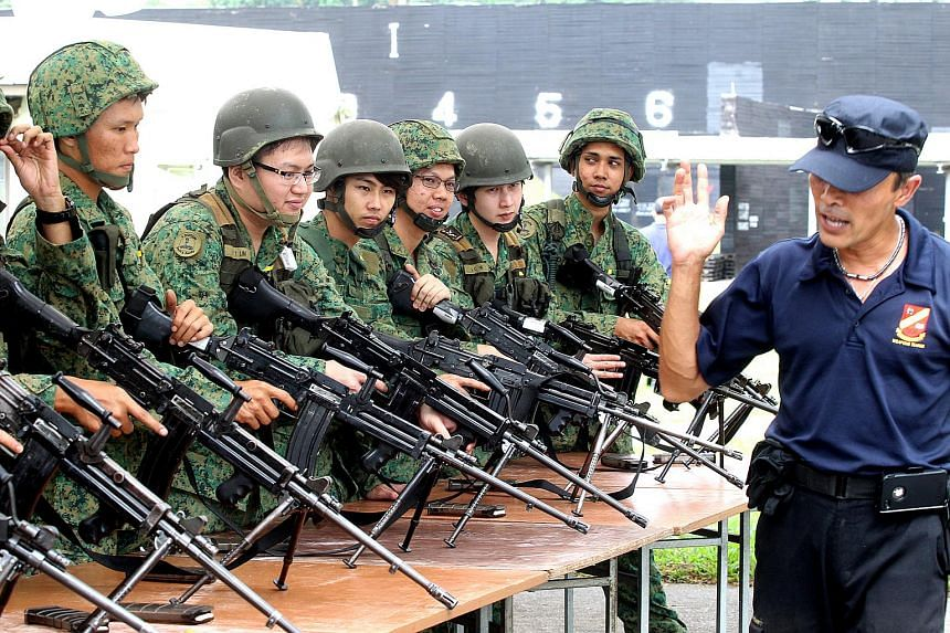 National servicemen (NSmen) inspecting their weapons before a live firing exercise during a mobilisation exercise at Nee Soon Camp.