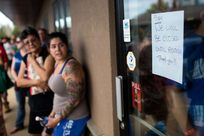 Residents of Fort McMurray line up outside a grocery store after they were ordered to be evacuated.