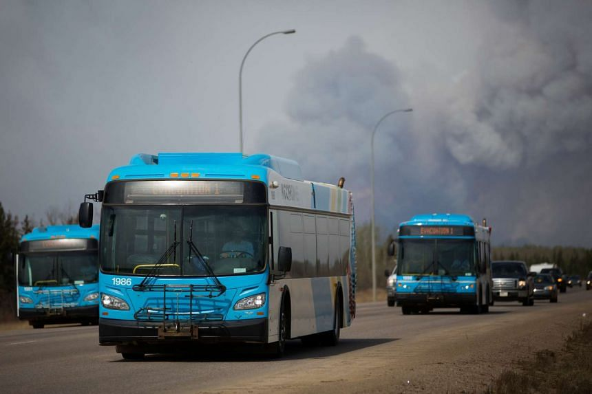 Vehicles drive away from Fort McMurray as winds pick up and smoke begins to darken, just south of Fort McMurray.