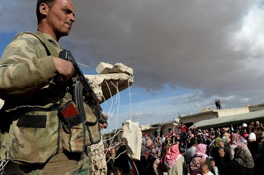 A soldier looks on as Syrians react to the arrival of a Russian military convoy in a small village near the city of Hama, on May 4, 2016.