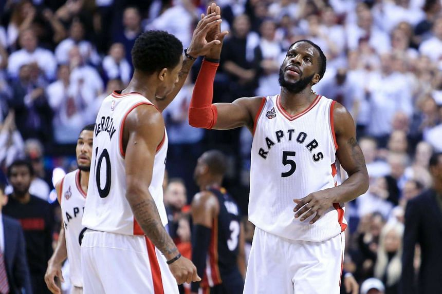 DeMar DeRozan (left) high-fives DeMarre Carroll (right) after Carroll scored in Game 2 of the Eastern Conference semi-finals, on May 5, 2016 in Toronto.
